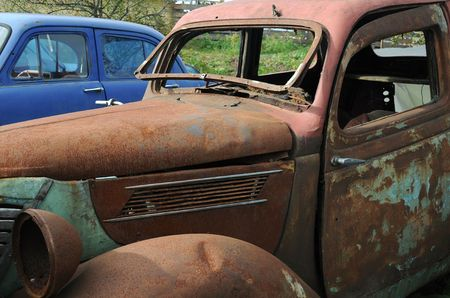Old and rusty cars in the junkyard photo