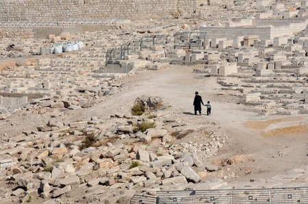 An old man and his grandson are walking down the cemetery in the Kidron Valley in Jerusalem, Israel