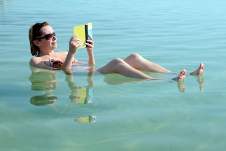 float: Caucasian woman reads a book floating in the waters of the Dead Sea in Israel
