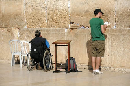 siddur: JERUSALEM, ISRAEL - NOVEMBER 10: A young Caucasian man and a handicapped person are praying at the Wailing Wall November 10, 2010 in Jerusalem, Israel.  Editorial