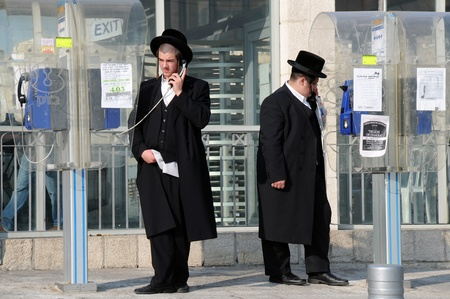 Two Othodox Jewish men talk on the phone in Jerusalem, Israel, on the 10th of November, 2010. Stock Photo - 8525933