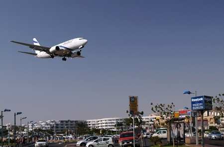 israeli: EILAT, ISRAEL - NOVEMBER 18: Passenger plane of Israeli airline flies low over the city of Eilat on the coast of the Red Sea seconds before safe landing in the airport November 18, 2010, Eilat, Israel Editorial