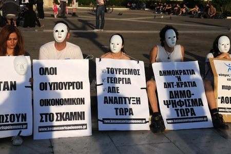 austerity: ATHENS, GREECE - MAY 9: People wearing white masks are protesting in the capital of Greece Athens outside the Parliament building against unpopular EU-IMF austerity deal May 9, 2010 in Athens, Greece
