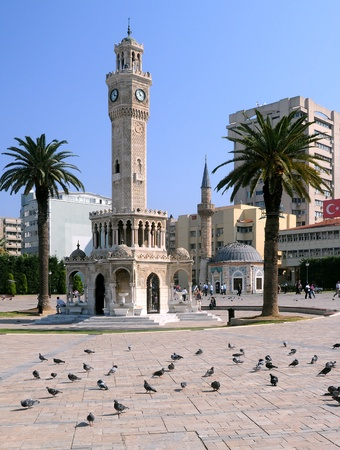 Historical clock tower, mosque and palm trees in Konak Square in the city of Izmir, Turkey