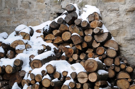 Stack of firewood covered with snow against stone wall background photo