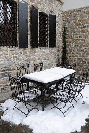 Table and chairs covered with snow in the empty street cafe  photo