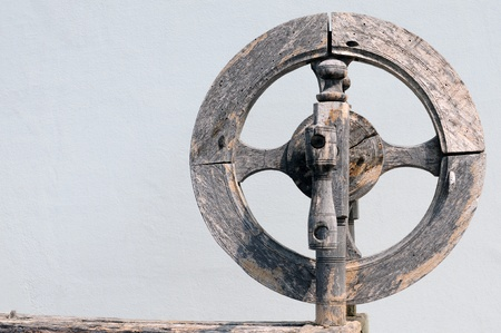 samsara: Vintage spinning wheel against white shabby wall background Stock Photo