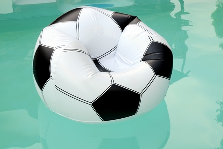floater: Floating rubber inflatable armchair resembling a soccer ball Stock Photo