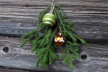 Christmas tree twig and decorations against the background of the shabby wooden wall photo
