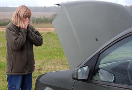 Caucasian woman is looking at the motor of her broken car in despair photo