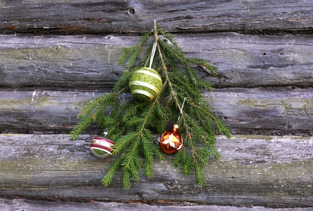 Christmas tree twig and decorations against the background of the wooden wall photo
