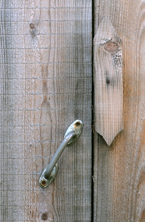 Wooden gate latch and metal handle on the shabby barn door photo