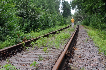 Caucasian lady walking down abandoned railroad track