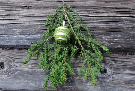 Cristmas tree twig and decoration against the shabby wooden wall background photo
