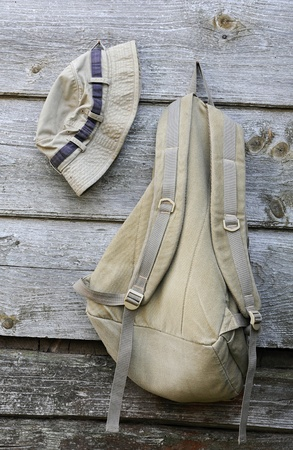 Hat and backpack of khaki color on the shabby wooden wall photo