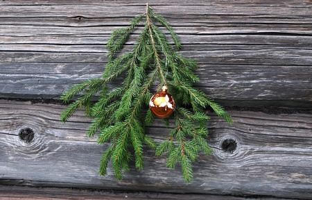 Christmas tree twig and decoration on the shabby wall of the wooden house photo