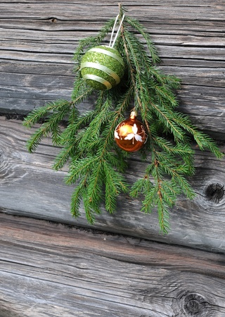Christmas tree twig and ornaments against the shabby wooden wall background photo