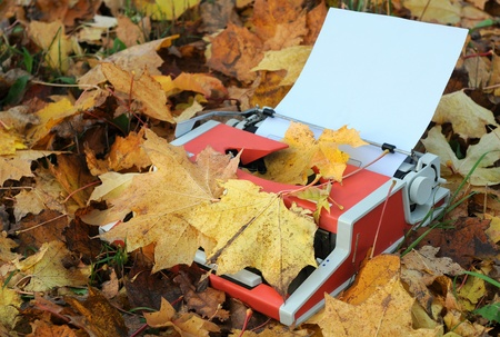 Vintage manual typewriter, blank sheet of paper and fallen maple leaves in the fall