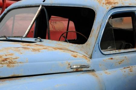 Close-up abandoned rusty blue car in the scrapeyard