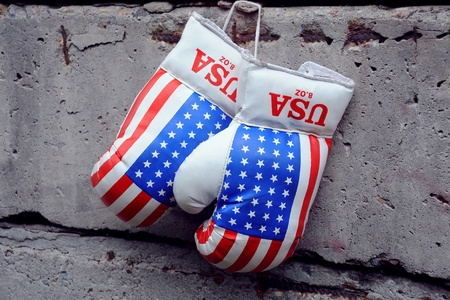 Used boxing gloves with US flag on them on the shabby concrete fence photo
