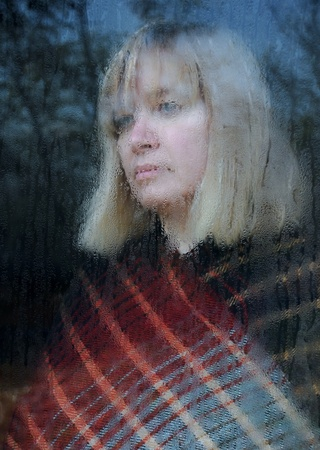 Portrait of the middle-aged woman looking through the window on a rainy day Stock Photo - 11274194