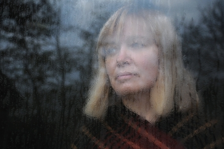 Portrait of the middle-aged woman looking through the window on a rainy day Stock Photo