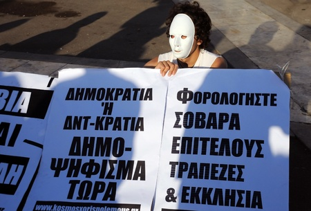 ATHENS, GREECE - MAY 9: Young man in white mask is protesting in the capital of  Greece Athens outside the Parliament building against unpopular EU-IMF austerity deal May 9, 2010 in Athens, Greece