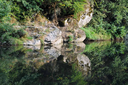 Rocky overgrown steep bank of the river reflected in the still water photo