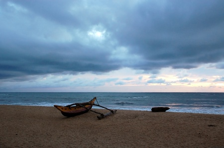 Fishing boat on the empty shore on a cloudy day in Sri Lanka at sunset photo