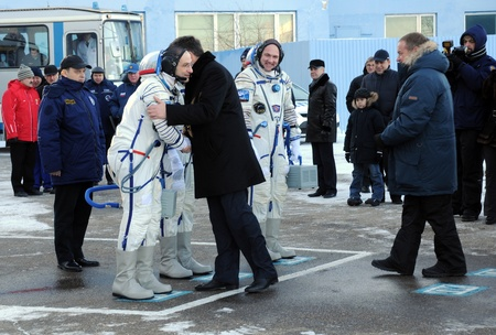 BAIKONUR, KAZAKHSTAN � DECEMBER 21: Don Pettit (NASA) is being embraced by head of Roscosmos Mr.Popovkin after ISS 31 crew flight readiness report Dec 21, 2011 at Baikonur cosmodrome, Kazakhstan  Stock Photo - 12779188