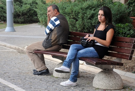 Young beautiful woman and middle-aged man are waiting for the bus in Izmir,Turkey, on the 1st of October, 2009