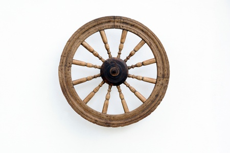 Vintage spinning wheel against the shabby white wall background Stock Photo - 13643460