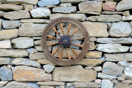 nonviolence: Vintage spinning wheel against stone wall background