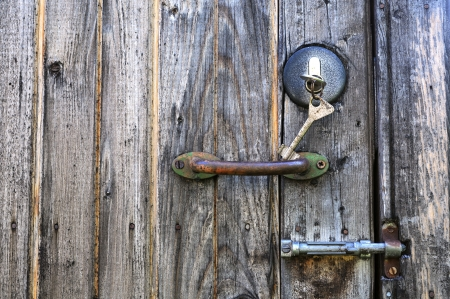 Keys in the lock, corroded handle and metal latch on the old wooden shabby door Stock Photo - 14382608