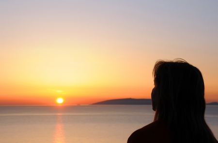 Silhouette profile of a woman looking at the sun rising from the sea Stock Photo