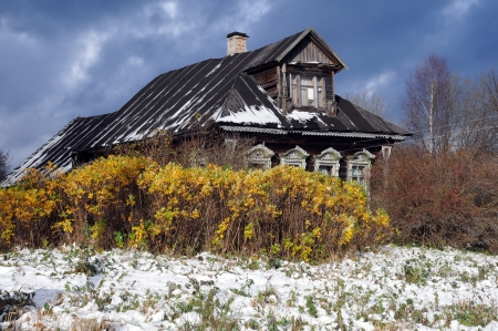 Old wooden village house, cloudy sky and first snow on the grass in Central Russia in the late fall Stock Photo - 15991940