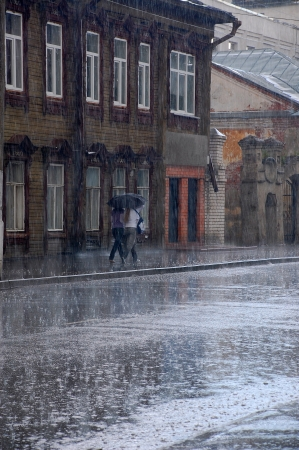 Two women walk in the rain down the street of the old Russian town Stock Photo