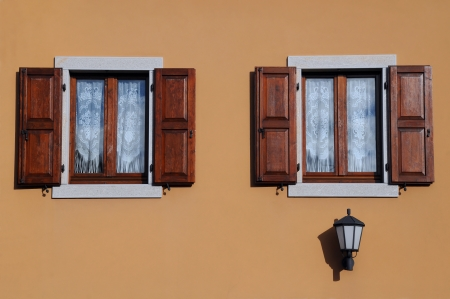 Two windows with shutters and street light against beige house wall background in Italy photo