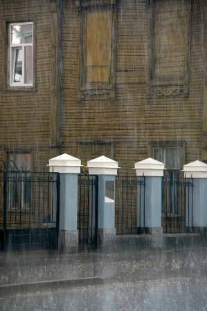 Part of the wooden house, fence and street in the rain in the old Russian city