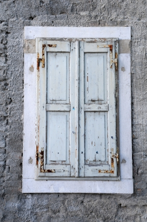 unpainted: Window with unpainted shutters against the rough house wall background Stock Photo