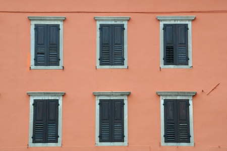 Windows with shutters against ochre house wal background in Italy photo
