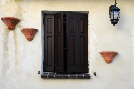 Window with shutters, cache-pots and street light against beige house wall background in Italy Stock Photo - 17044640