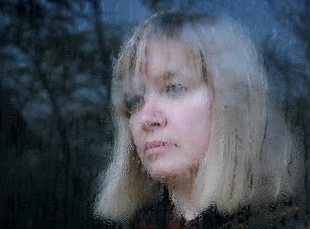 looking through window: Blurred portrait of the middle-aged woman looking through the window on a rainy day Stock Photo