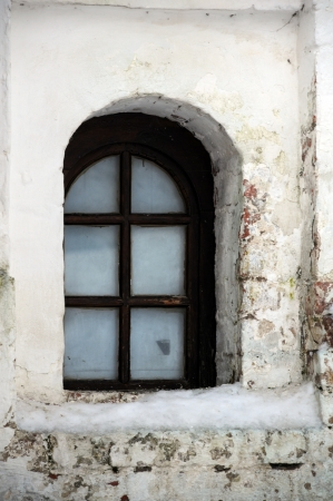 Window and uncared wall in medieval convent in Central Russia photo