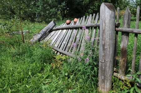 Old broken tilted fence in the Russian village photo