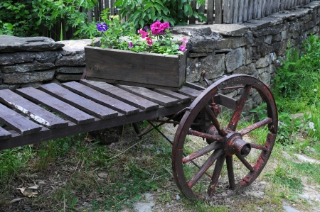 Parte de la vieja carreta y flores en la caja de la flor en Bulgaria Foto de archivo - 20049367