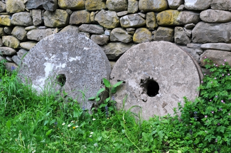 millstone: Two old millstones against the stone wall Stock Photo
