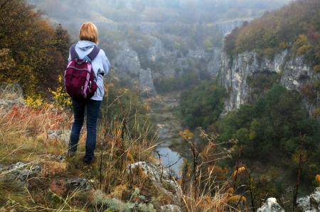A woman stands on the edge of Emen canyon in Bulgaria on a raw foggy morning in the fall photo