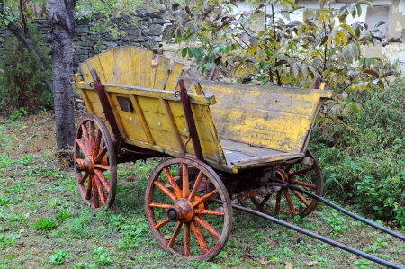 Old shabby wooden yellow cart in the garden  Stock Photo - 23181039