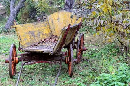 Old shabby wooden yellow cart in the garden photo